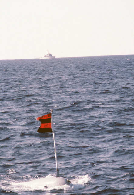 """A minesweeping float, also known as a""""pig,""""is towed through the water druing a training exercise.  The ocean minesweeper USS FEARLESS (MSO 442) is in the background.  The FEARLESS is one of three minesweepers being towed to the Persian Gulf by the salvage ship USS GRAPPLE (ARS 53) to support US Navy escort operations"""