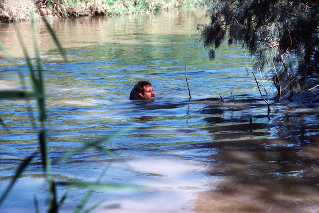 A Sea-Air-Land (SEAL) team member crosses a stream during a field training exercise