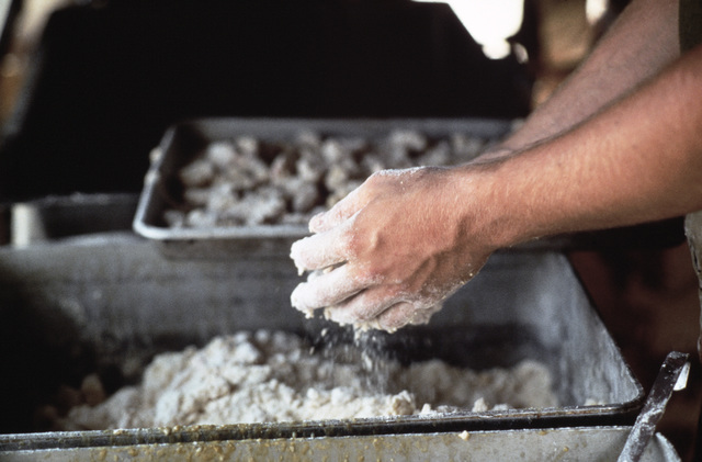 A serviceman prepares batter to cook shrimp at the field kitchen during Exercise SHADOW HAWK'87, the Jordan/US segment of BRIGHT STAR'87.  SHADOW HAWK is a combined effort of the Joint Chiefs of STAFF/US Central Command