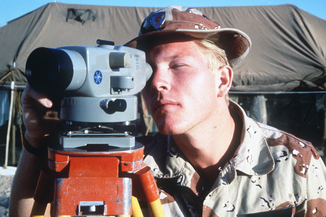 AIRMAN (AMN) First Class Mark Starr, a surveyor with the 823rd Civil Engineering Squadron, uses a theodolite to determine the parameters for the base site to be used by Red Horse personnel during Exercise SHADOW HAWK'87, a phase of BRIGHT STAR'87.  The US