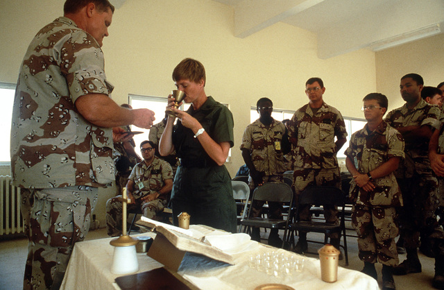 Chaplain (LT. COL.) James Mackey administers Communion during Protestant religious services conducted for the exercise Shadow Hawk segment of Bright Star '87. In this U.S. Central Command/Joint Chiefs of STAFF exercise, U.S. forces operate with the Jordan