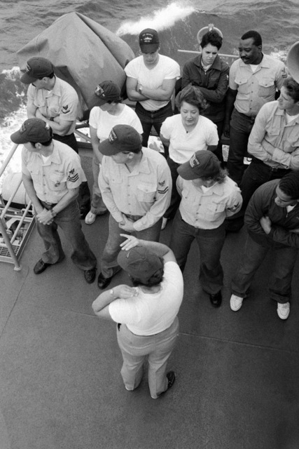 Crew members are given a briefing aboard the salvage ship USS GRAPPLE (ARS 53). The GRAPPLE is towing three minesweepers to the Persian Gulf to support US Navy escort operations