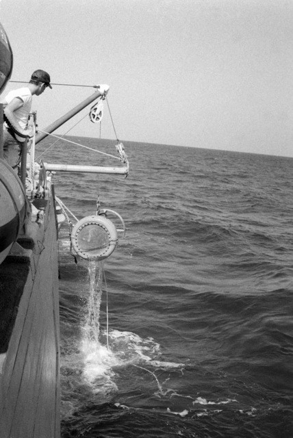 Crew members hoist an acoustical device from the water onto the ocean minesweeper USS ILLUSIVE (MSO 448) during a training exercise. The ILLUSIVE is one of three minesweepers being towed to the Persian Gulf to support US Navy escort operations
