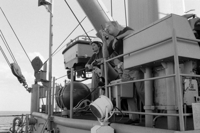 Crew members oversee towing operations from the bridge wing of the salvage ship USS GRAPPLE (ARS 53). The GRAPPLE is towing three minesweepers to the Persian Gulf to support US Navy escort operations