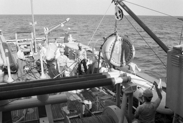 Crew members prepare to lower an acoustical device into the water from the ocean minesweeper USS ILLUSIVE (MSO 448) during a training exercise. The ILLUSIVE is one of three minesweepers being towed to the Persian Gulf to support US Navy escort operations