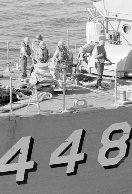 Crew members stand by on the deck of the ocean minesweeper USS ILLUSIVE (MSO 448) during a training exercise. The ILLUSIVE is one of three minesweepers being towed to the Persian Gulf to support US Navy escort operations