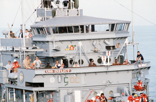 Crew members watch from the bridge of the ocean minesweeper USS INFLICT (MSO 456) as crewmen from the salvage ship USS GRAPPLE (ARS 53) hook up a towing rig.  The INFLICT is one of three minesweepers being towed to the Persian Gulf by the USS GRAPPLE to support US Navy escort operations