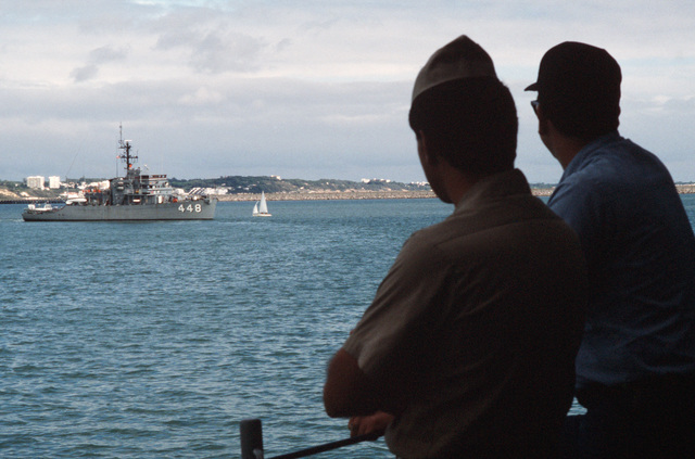 Crew members watch from the rail the salvage ship USS GRAPPLE (ARS 53) as the ocean minesweeper USS ILLUSIVE (MSO 448) leaves port.  The ILLUSIVE is one of three minesweepers being towed to the Persian Gulf by the GRAPPLE to support US Navy escort operations