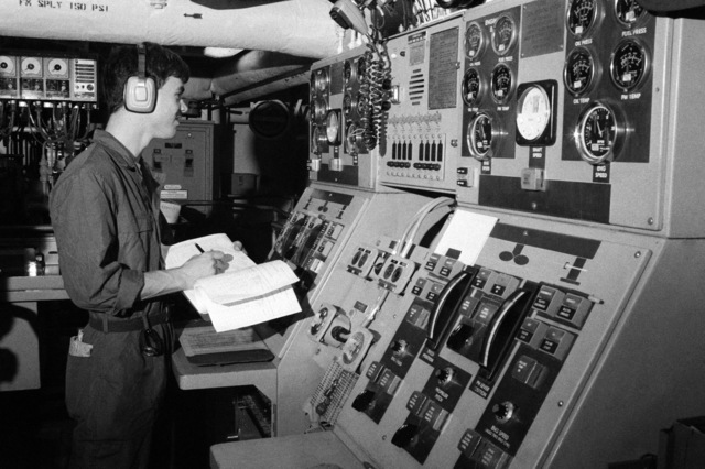 Electrician's Mate 3rd Class Earl Stout monitors power plant control stations aboard salvage ship USS GRAPPLE (ARS 53). The GRAPPLE is towing three minesweepers to the Persian Gulf to support US Navy escort operations