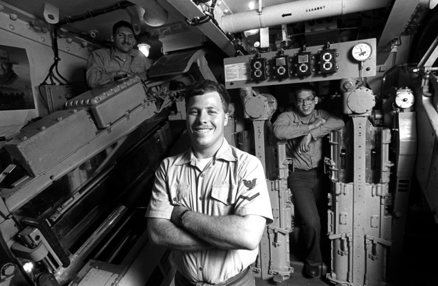 GUNNER's Mate (Guns) 3rd Class Scott Leach, mount captain, Gunners Mate (Guns) SEAMAN Darrin Seiger, mount pointer, and GUNNER's Mate (Guns) SEAMAN Joseph Dobbins, mount trainer, pose for a photo inside the turret of the Mount 51 Mark 28 five-inch/38 caliber gun aboard the USS IOWA (BB-61)