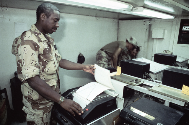 Inside the message preparation van, STAFF Sergeant (SSGT) Mayfield Parker checks a printout to ensure that messages going into and out from Jordan are being transmitted without any characters missing.  The telecommunications operator from the Joint Commun