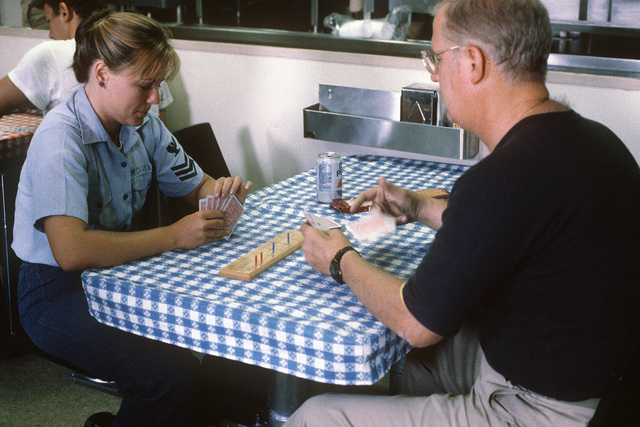 Lieutenant Commander (LCDR) commanding officer of the salvage ship USS GRAPPLE (ARS 53), plays a hand of cribbage with a crew member.  The GRAPPLE is towing three minesweepers to the Persian Gulf to support US Navy escort operations