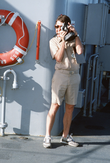 Lieutenant (LT) Sternberg, Medical Corps, takes a photograph while aboard the salvage ship USS GRAPPLE (ARS 53).  The GRAPPLE is towing three minesweepers to the Persian Gulf to support US Navy escort operations