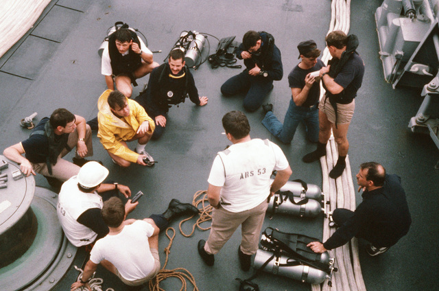 Members of a dive team conduct a safety briefing aboard the salvage ship USS GRAPPLE (ARS 53) before making a survey dive on an ocean minesweeper.  The GRAPPLE is towing three minesweepers to the Persian Gulf to support US Navy escort operations
