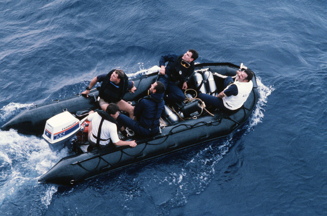 Members of a dive team from the salvage ship USS GRAPPLE (ARS 53) use an inflatable boat to take them to an ocean minesweeper for a survey dive.  The GRAPPLE is towing three minesweepers to the Persian Gulf to support US Navy escort operations