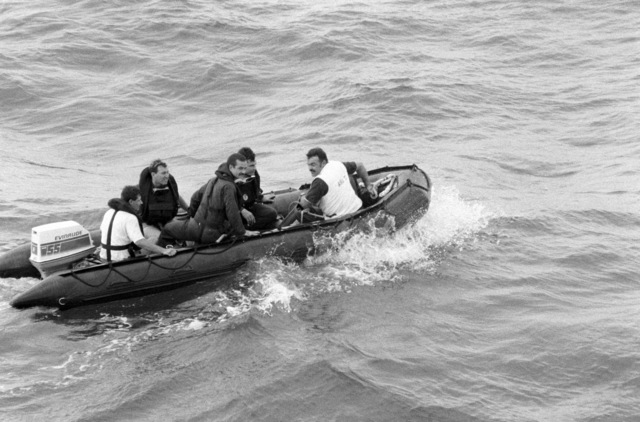 Members of a dive team from the salvage ship USS GRAPPLE (ARS 53) use an inflationable boat to take them to an ocean minesweeper for a survey dive. The GRAPPLE is towing three minesweepers to the Persian Gulf to support US Navy escort operations