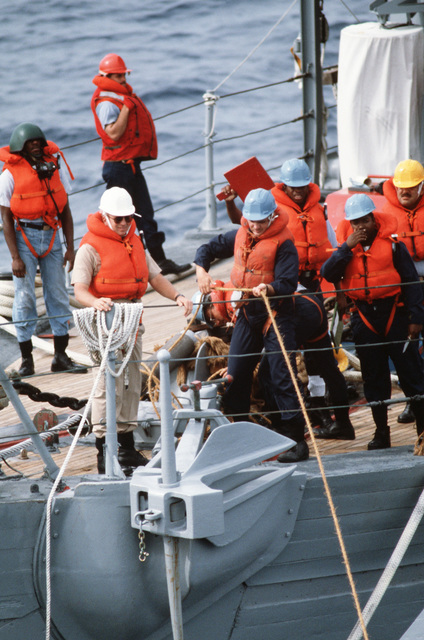 Members of a rig crew handle lines on the bow of the ocean minesweeer USS FEARLESS (MSO 442).  The FEARLESS is one of the three minesweepers being towed to the Persian Gulf to support US Navy escort operations