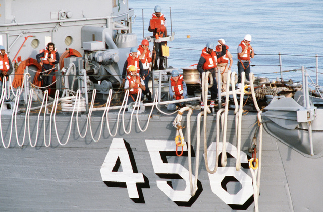 Members of a rig crew stand by on the bow of the ocean minesweeper USS INFLICT (MSO 456).  The INFLICT is one of three minesweepers being towed to the Persian Gulf by the USS GRAPPLE (ARS 53) to support US Navy escort operations