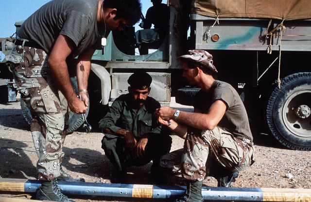 Members of the US and Jordanian military separate tent poles for repacking as the camp prepares for redeployment at the conclusion of Exercise SHADOW HAWK'87, a phase of BRIGHT STAR'87.  The US Central Command exercise represents a Joint Chiefs of STAFF e