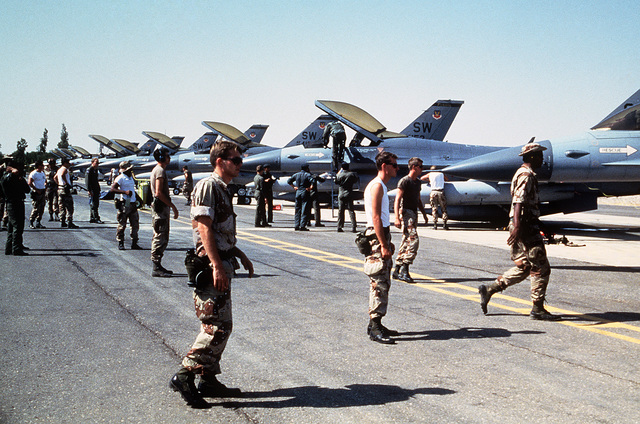 Members of the US military walk toward F-16 Fighting Falcon aircraft parked on the flight line during Exercise SHADOW HAWK'87, a phase of BRIGHT STAR'87.  The US Central Command exercise represents a Joint Chiefs of STAFF effort to evaluate procedures use