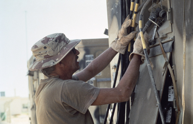 Preparing for redeployment, Sergeant First Class (SFC) James Puckett of US Central Command unplugs telephone cable from the TTC-39 communications trailer which supported the joint Jordan/US Exercise SHADOW HAWK'87, a part of Exercise BRIGHT STAR'87.  SHAD