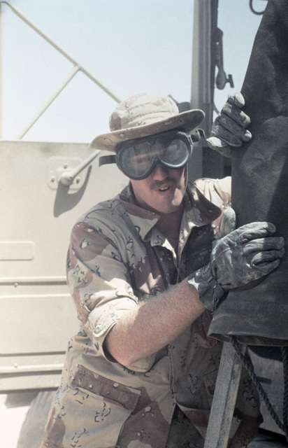 Private First Class (PFC) Michael Hendry seeks cover behind equipment in a dust storm during the Exercise SHADOW HAWK'87, segment of BRIGHT STAR'87.  In this US Central Command/Joint Chiefs of STAFF exercise, US forces operate with the Jordanian military