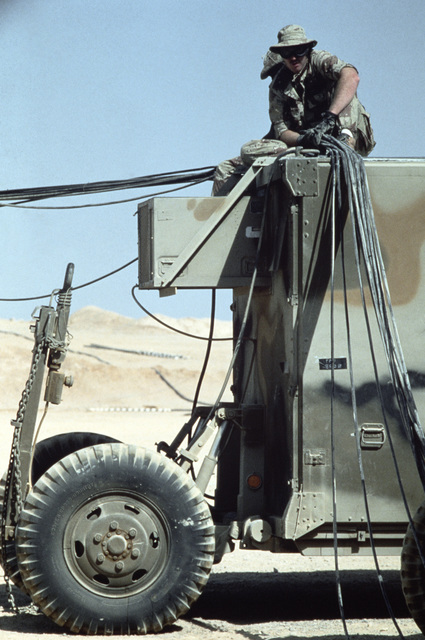 Private First Class (PFC) Mike Hendry of the Joint Communications Support Element disconnects cables at the main communications trailer area.  His unit is preparing to redeploy from Exercise SHADOW HAWK'87 to its parent Exercise BRIGHT STAR'87, in Egypt