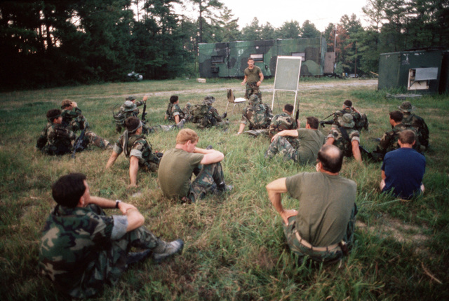 Sea-Air-Land (SEAL) team members listen to an instructor in an open-field classroom during a field training exercise