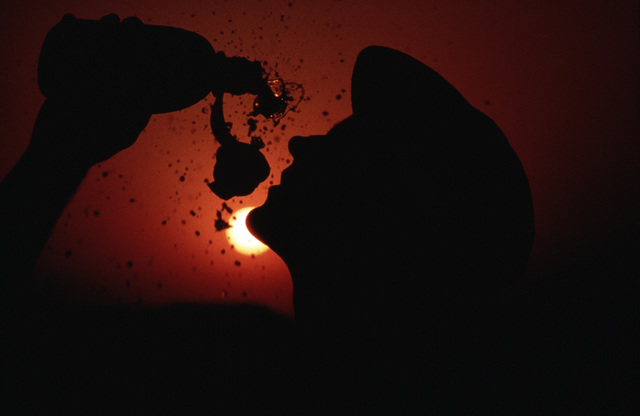 SENIOR AIRMAN (SRA) Brad Dirks of the Detachment 7, 1361st Audiovisual Squadron, is silhouetted against the setting sun as he pours water on his face to cool off.  He is participating in the Exercise SHADOW HAWK'87.  In this US Central Command/Joint CHIEF