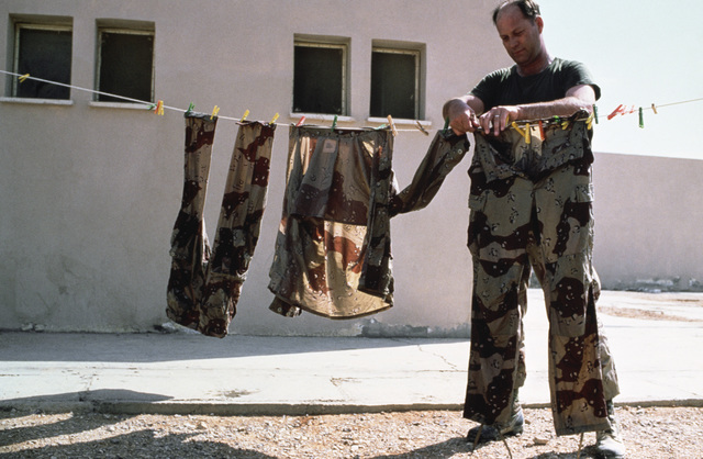SENIOR MASTER Sergeant (SMSGT) David Pruitt of the Defense Communications Agency-Europe hangs his laundry on a clothesline outside his barracks during Exercise SHADOW HAWK'87, the Jordan/US segment of Exercise BRIGHT STAR'87.  SHADOW HAWK is a combined ef