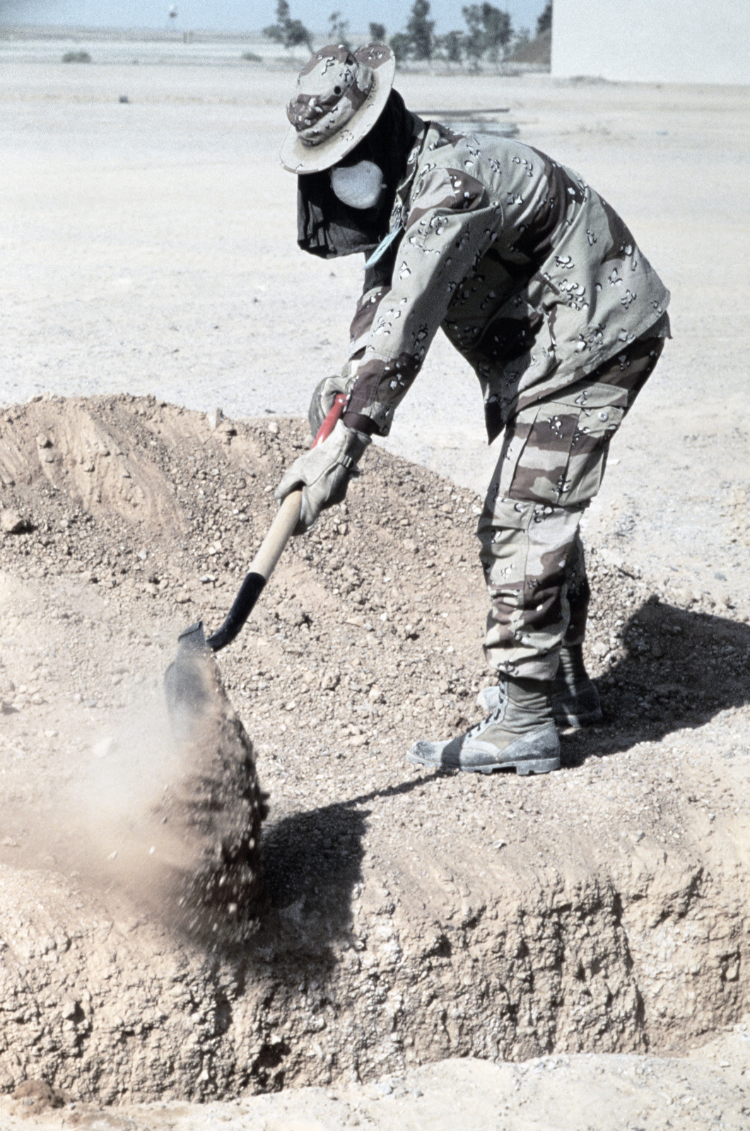 Sergeant (SGT) Bruce Gibson of the 56th Medical Squadron shovels dirt to fill in a field latrine during Exercise SHADOW HAWK'87.  In this US Central Command/Joint Chiefs of STAFF exercise, US forces operate with the Jordanian military in a desert environm