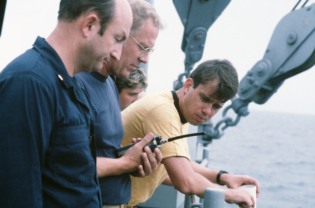 Ship's officers observe rigging operations aboard the salvage ship USS GRAPPLE (ARS 53).  The GRAPPLE is towing three minesweepers to the Persian Gulf to support US Navy escort operations