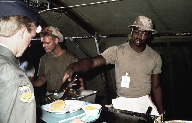 SPECIALIST Fourth Class Mike Owens of the 2nd Battalion, 34th Infantry Divison, serves up pancakes at the field conditions chow hall during Exercise SHADOW HAWK'87, the Jordan/US segment of BRIGHT STAR'87.  SHADOW HAWK is a combined effort of the Joint Ch