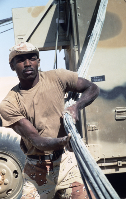 SPECIALIST Fourth Class (SPC) Dewayne Clark of the Joint Communications Support Element pulls down cables from communications trailers used in the joint Jordan/US Exercise SHADOW HAWK'87.  He is preparing for redeployment to Exercise BRIGHT STAR'87.  SHAD