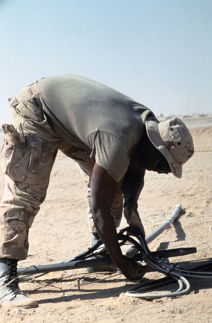 SPECIALIST Fourth Class (SPC) Dewayne Clark of the Joint Communications Support Element sets down cables removed from the communications trailers used in the joint Jordan/US Exercise SHADOW HAWK'87, as he prepares for redeployment to Exercise BRIGHT STAR'