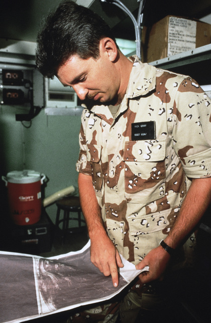 STAFF Sergeant (SSGT) Rick E. Gray, Joint Communications Support Element, checks a weather chart during Exercise SHADOW HAWK'87, a phase of BRIGHT STAR'87.  The US Central Command/Joint Chiefs of STAFF exercise provides US forces with the opportunity to o