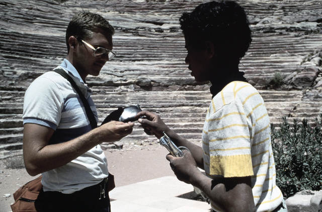 STAFF Sergeant (SSGT) Scott Stewart of the Audiovisual Squadron, on a tour provided by the Jordanian military for US participants in the joint Exercise SHADOW HAWK'87, examines wares offered by a youth.  The US Central Command/Joint Chiefs of STAFF exerci