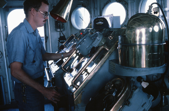 Storekeeper 2nd Class Randy Summers stands watch at the helm of the the ocean minesweeper USS ILLUSIVE (MSO 448).  The ILLUSIVE is one of three minesweepers being towed to the Persian Gulf by the salvage ship USS GRAPPLE (ARS 53) to support US Navy escort operations