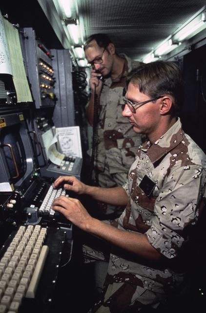Technical Sergeant (TSGT) Jerry Ackley of the Joint Communications Support Element, foreground, programs land telephone lines inside the ANTTC Automatic Circuit Switcher van set up for Exercise SHADOW HAWK'87, a joint Jordan/US Exercise within Exercise BR