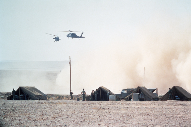 UH-60 Black Hawk (Blackhawk) helicopters stir up dust in the base camp during Exercise SHADOW HAWK'87,  a phase of Exercise BRIGHT STAR'87.  The exercise will evaluate procedures used to deploy US tactical and logistical forces