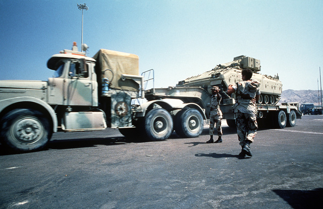 U.S. military personnel direct the driver of a tank transporter which is moving an M-2 Bradley infantry fighting vehicle for redeployment to Egypt at the conclusion of Exercise Shadow Hawk, a phase of Bright Star '87. The U.S. Central Command/Joint Chiefs of STAFF exercise provided U.S. forces with the opportunity to operate with Jordanian military forces, work in a desert environment and check the effectiveness of a joint communications network
