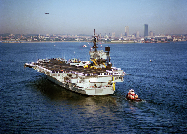 A port quarter view of the aircraft carrier USS JOHN F. KENNEDY (CV 67) entering Boston Harbor with sailors manning the rails