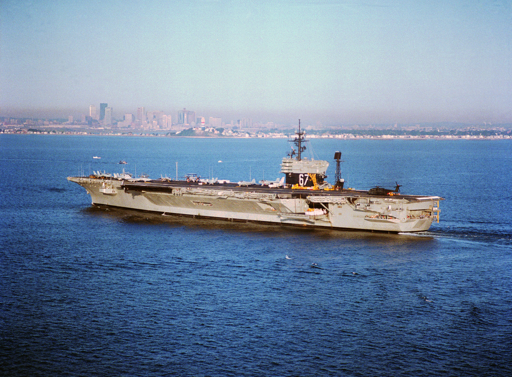 A port quarter view of the aircraft carrier USS JOHN F. KENNEDY (CV 67) entering Boston Harbor