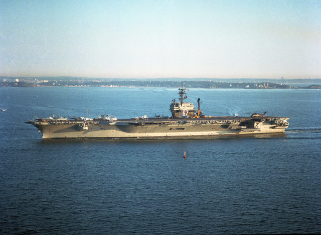 A port view of the aircraft carrier USS JOHN F. KENNEDY (CV 67) entering Boston Harbor