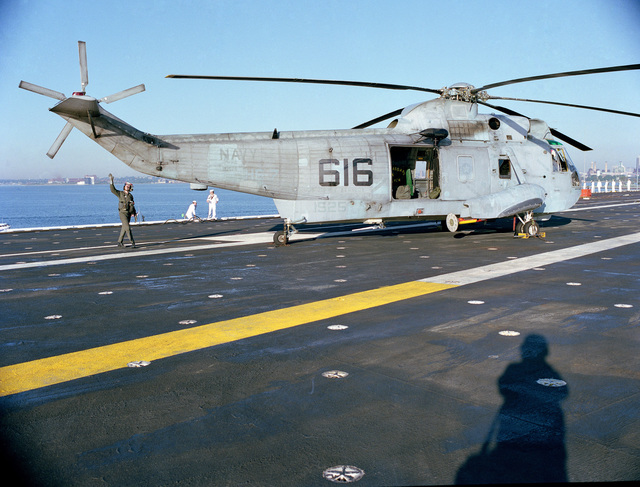 A SH-3H Sea King helicopter from Helicopter Anti-submarine Squadron 7 (HS-7) is parked on the flight deck of the aircraft carrier USS JOHN F. KENNEDY (CV 67) as it enters Boston Harbor with sailors manning the rail in the background