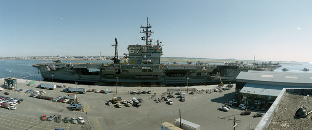 A starboard beam view of the aircraft carrier USS JOHN F. KENNEDY (CV 67) tied up at a pier. The ship held an open house during its stay in port