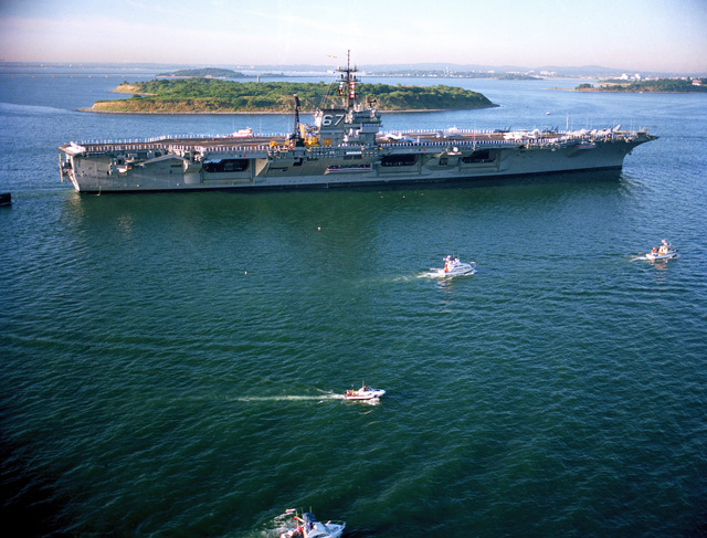 A starboard view of the aircraft carrier USS JOHN F. KENNEDY (CV 67) entering Boston Harbor with sailors manning the rail