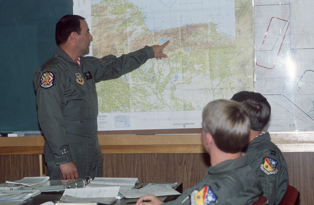 Major (MAJ) George Cella, center, of the 430th Tactical Fighter Squadron, briefs his flight team on weather conditions, flight plans and estimated arrival times for their deployment to El Libertador Air Base, Venezuela, for a two-week training exercise with members of Group 16 of the Venezuelan air force.  Members of the team include Captain (CPT) Tom Sykes, Lieutenant (LT) Rick Davis and LT John Park