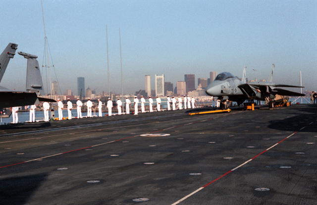 Sailors of the aircraft carrier USS JOHN F. KENNEDY (CV 67) man the rails as the ship enters Boston Harbor
