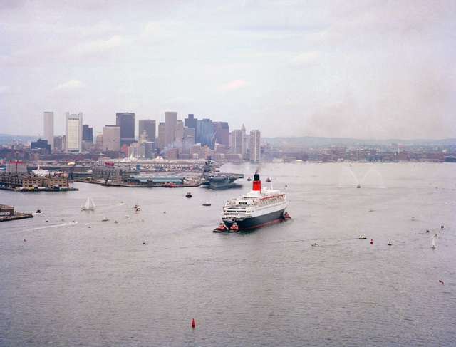 As the RMS QUEEN ELIZABETH II enters the harbor it passes by the aircraft carrier USS JOHN F. KENNEDY (CV 67) which is preparing to leave port